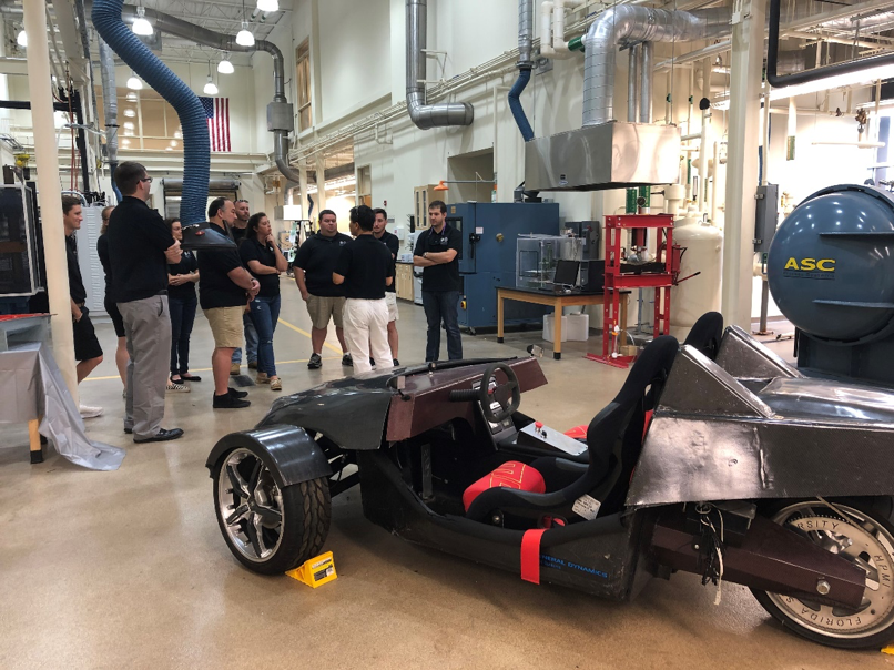 3 MSSE students and faculty tour HPMI, carbon fiber electric vehicle.png