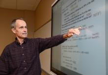 Male ECE faculty at smart board in classroom
