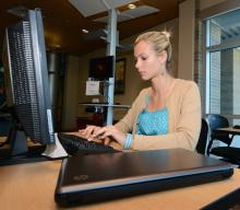 Female student at computer station in library