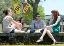 Mixed-gender students sitting on amphitheater wall