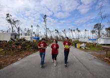Students carry Hurricane Michael recovery supplies down a street