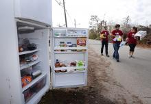 Open refrigerator door, students carry food to areas effected by Hurricane Michael