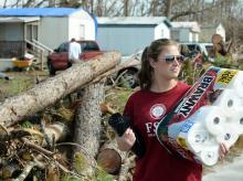 Student carrying supplies to neighborhoods recovering from hurricane