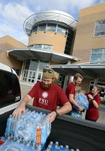 Students load vehicles with hurricane recovery supplies