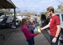 Student hands out supplies to hurricane survivor